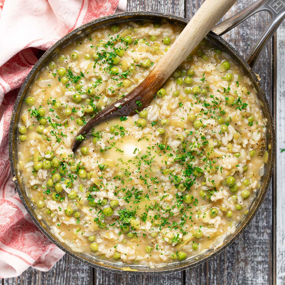 cooked risi e bisi (Italian rice and peas) in a pan topped with some melting butter and fresh chopped parsley