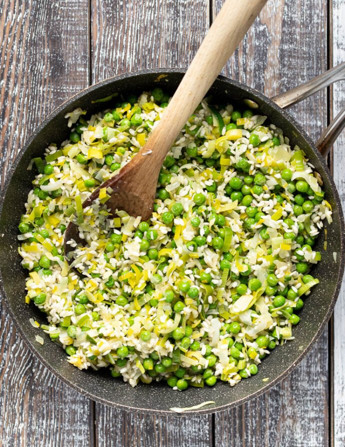 risotto rice, peas, onions and leeks cooking in a pan