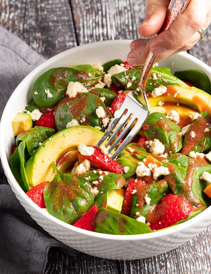 a fork digging in to a bowl of strawberry spinach salad
