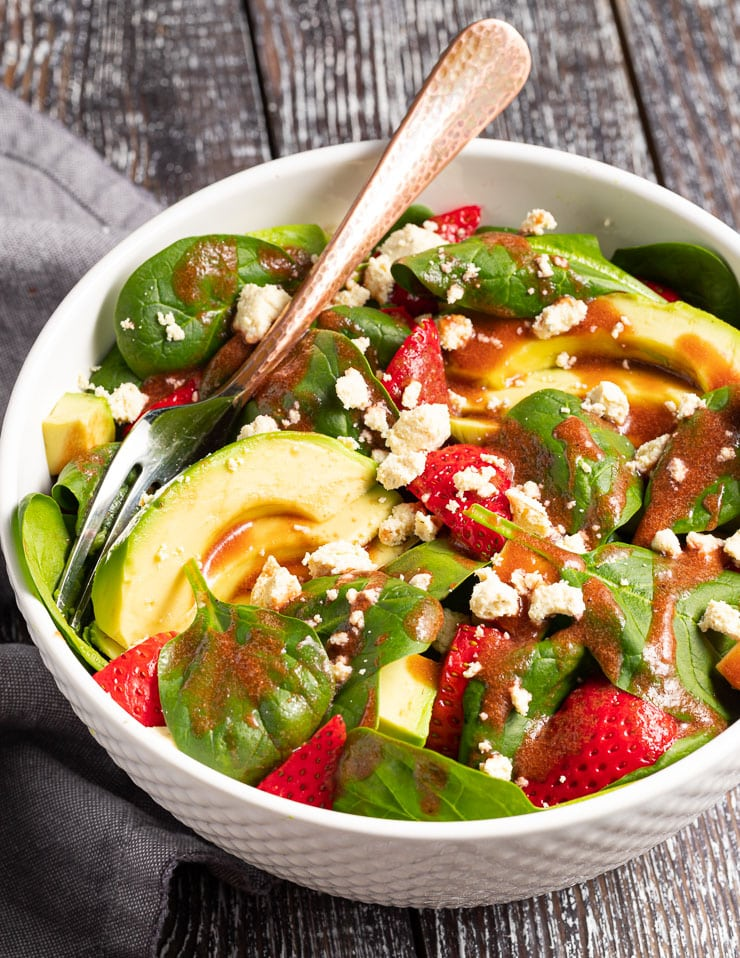 a bowl of strawberry spinach salad with avocado and vegan feta, drizzled in vinaigrette