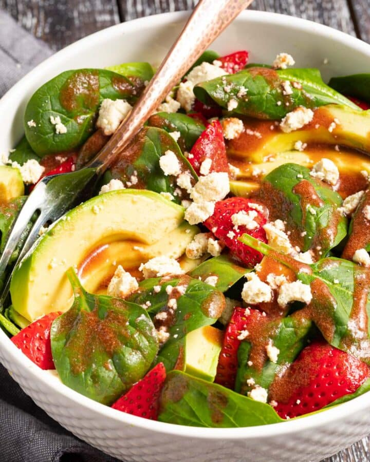a bowl of strawberry spinach salad with avocado and vegan feta drizzled in strawberry vinaigrette