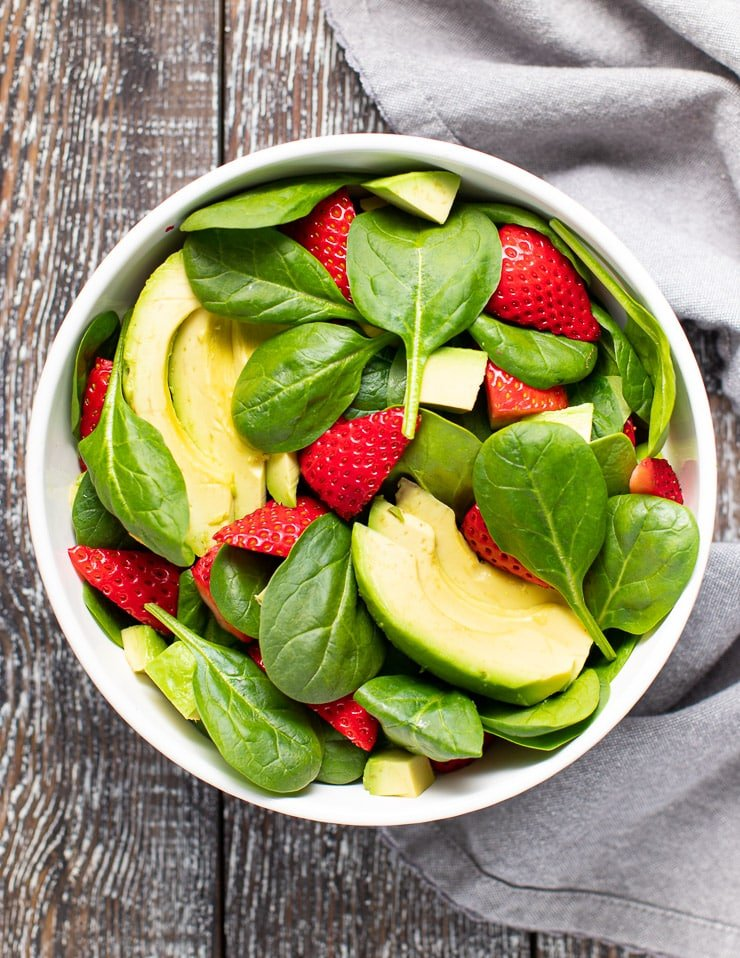 spinach strawberries and avocado in a bowl
