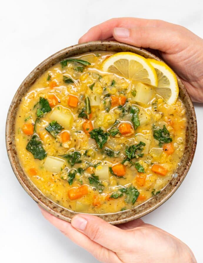 two hands holding a bowl of red lentil soup with lemon
