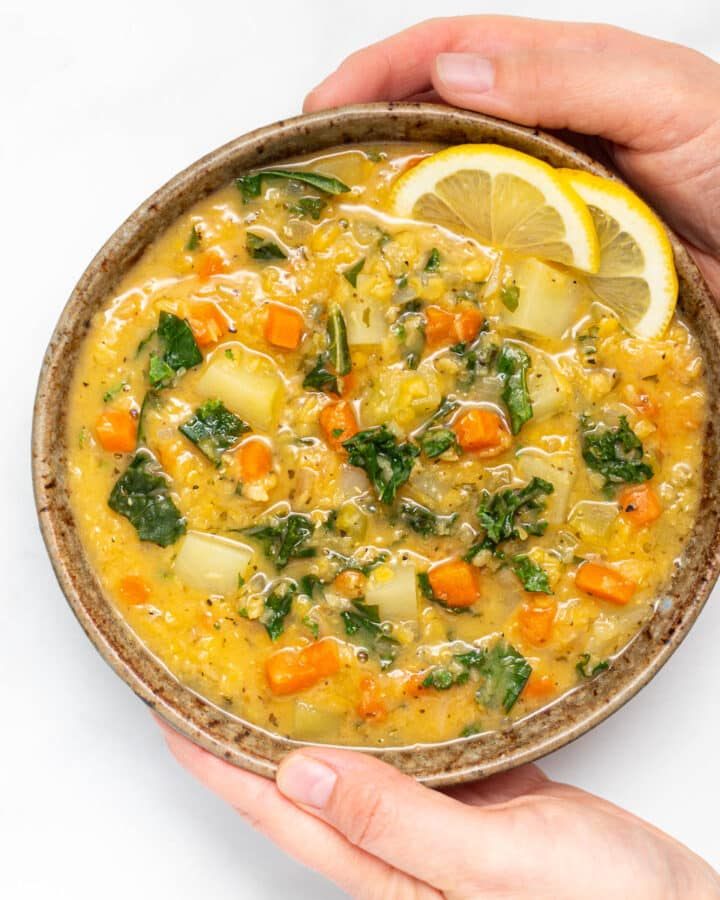 A bowl of lemony red lentil soup with a lemon slice garnish being held by 2 hands
