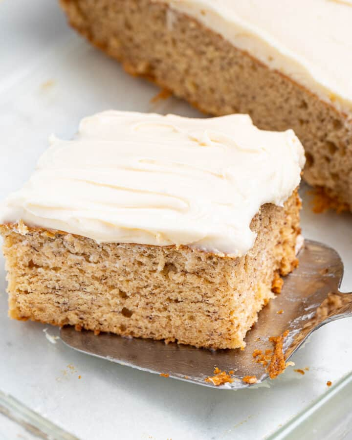 a slice of vegan banana cake being lifted out of a glass dish with a spatula