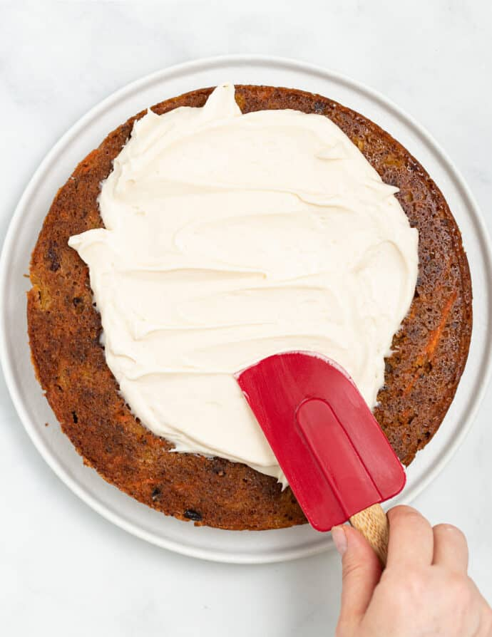 vegan cream cheese frosting being spread on a cake layer with a spatula