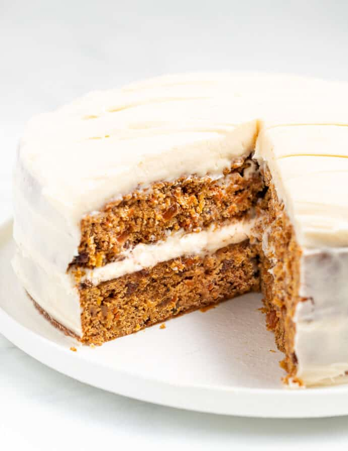 a vegan carrot cake on a plate with one slice cut out, inside showing