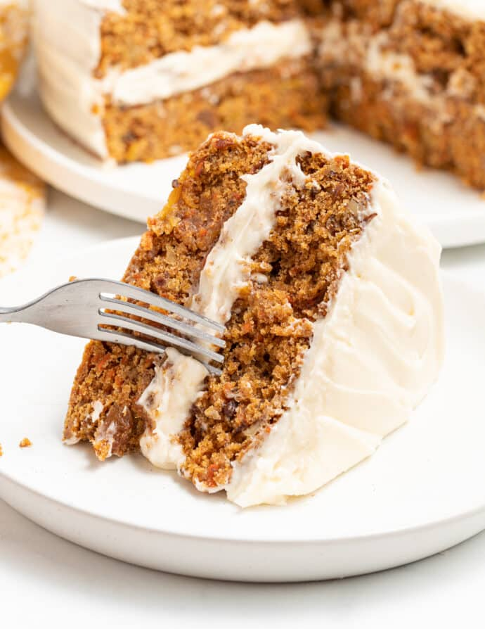 a spice of carrot cake on a plate with a fork cutting into it