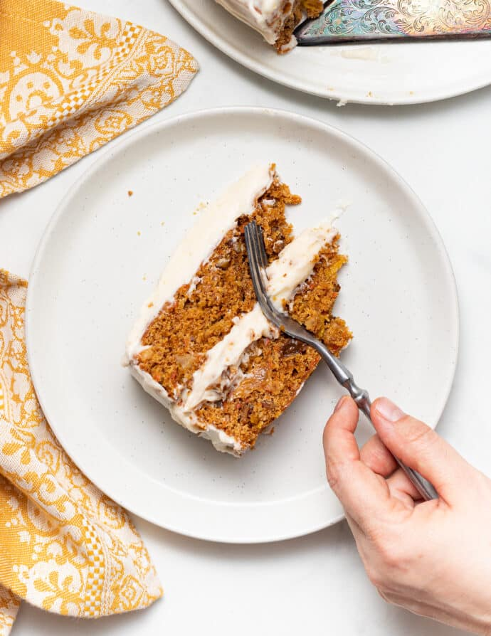 overhead shot of a part eaten piece of carrot cake with a hand holding a fork
