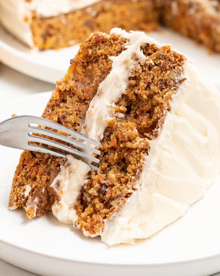 a slice of frosted vegan carrot cake on a plate