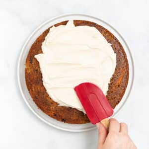 vegan cream cheese frosting being spread on a carrot cake