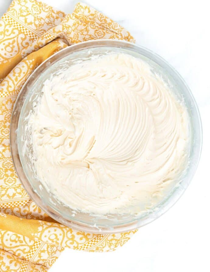 a bowl of vegan cream cheese frosting with pretty patterns from the whisk