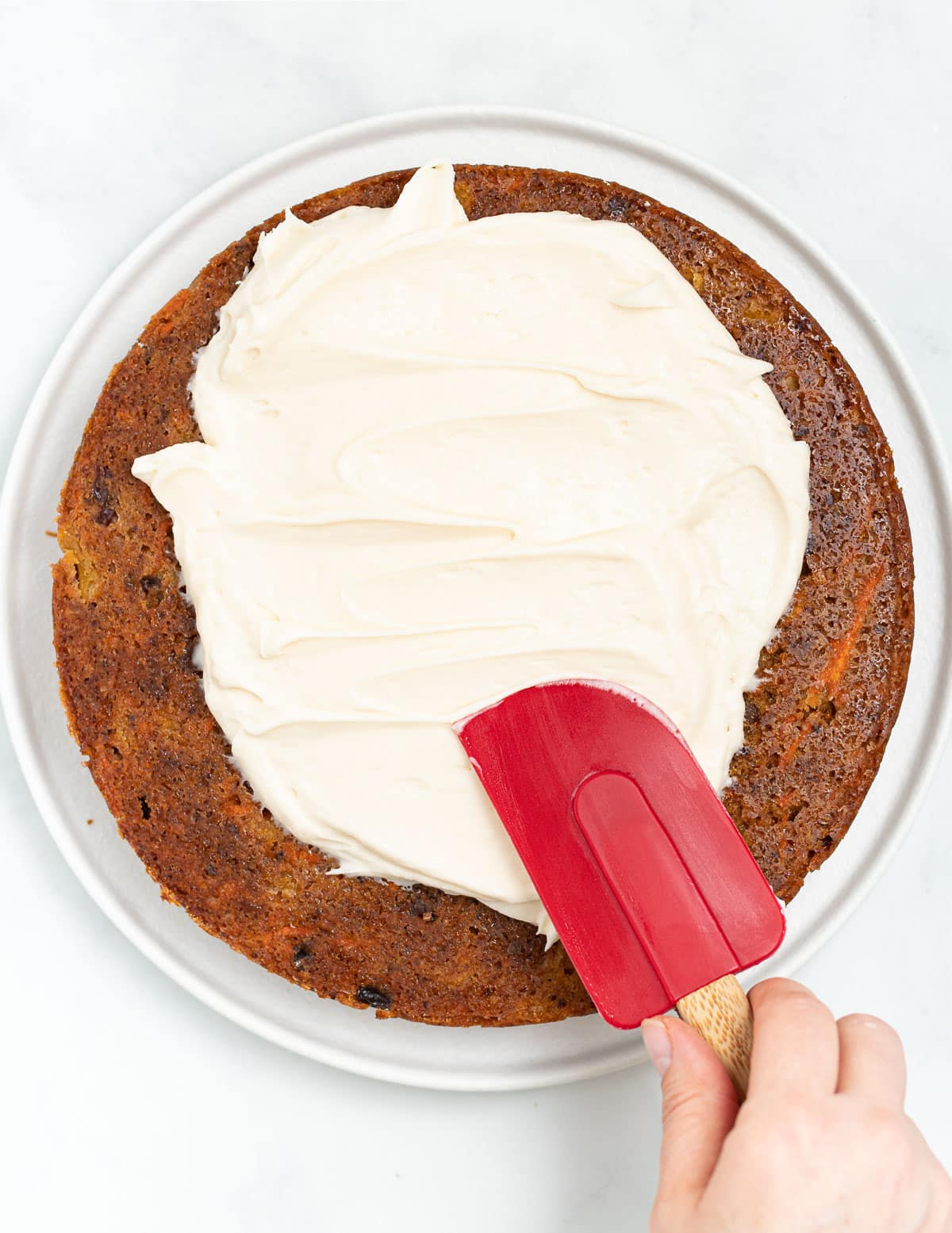 vegan cream cheese being spread on a cake layer with a red spatula