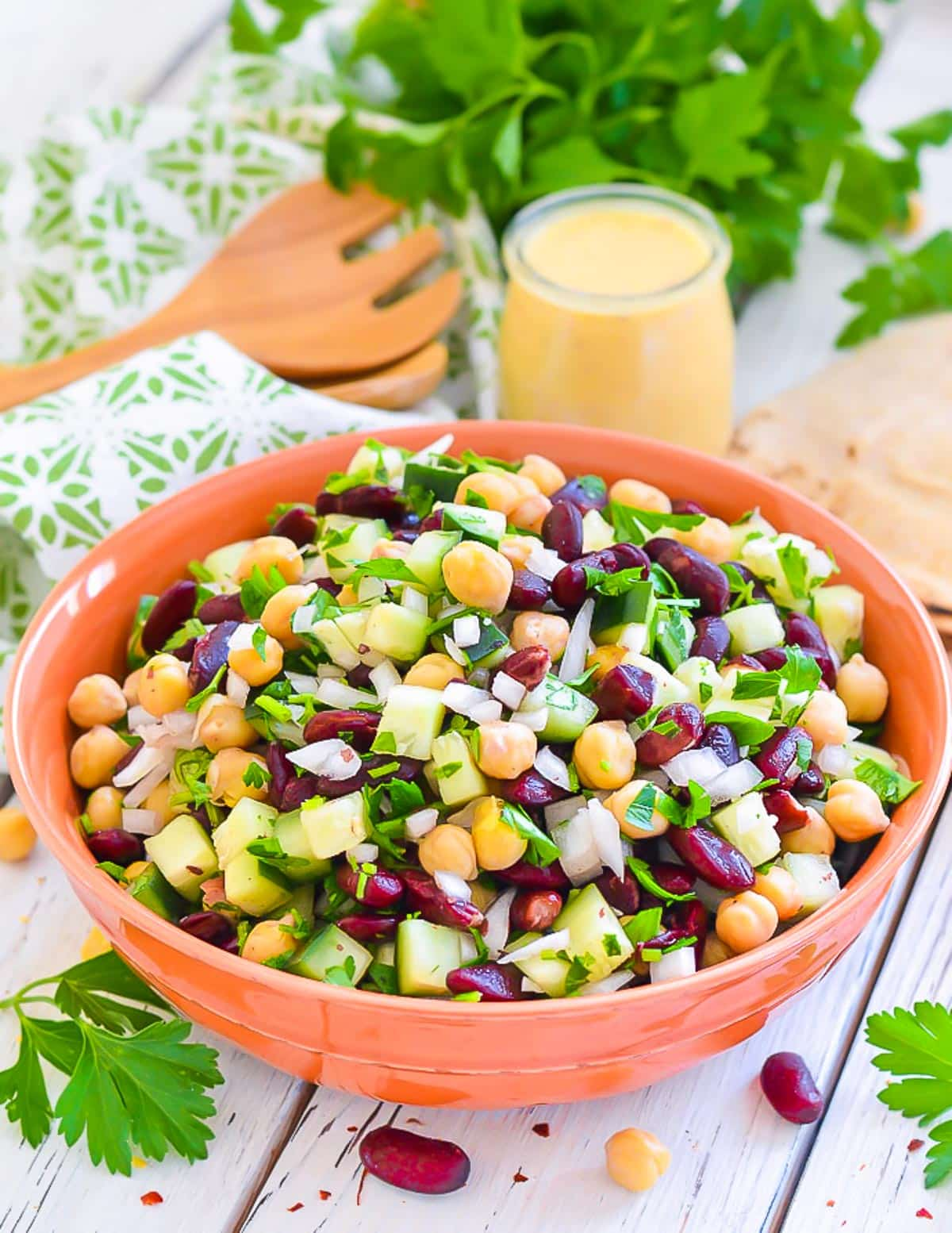 kidney bean salad in a bowl with a jar of lemon dressing behind