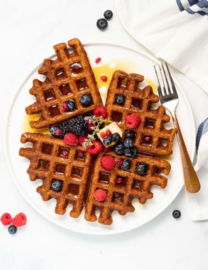 oatmeal waffles topped with fresh berries and syrup on a white plate