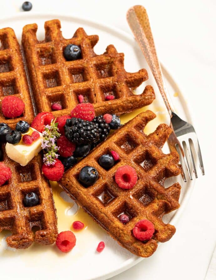 oatmeal waffles and fresh berries with a fork on a plate