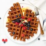 4 oatmeal waffles topped with syrup, raspberries, blackberries and blueberries