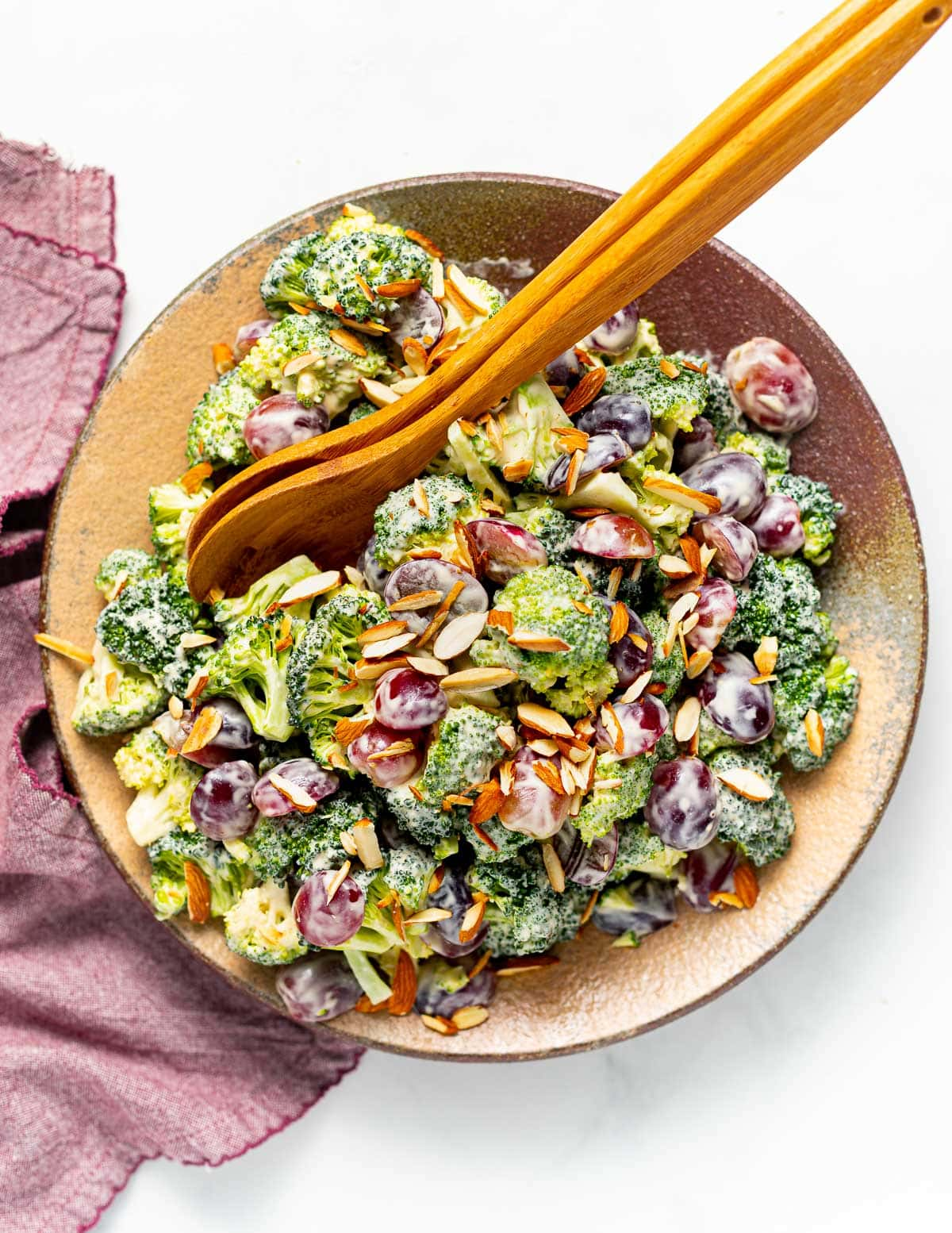 a plate of vegan broccoli salad with wooden salad servers resting across it