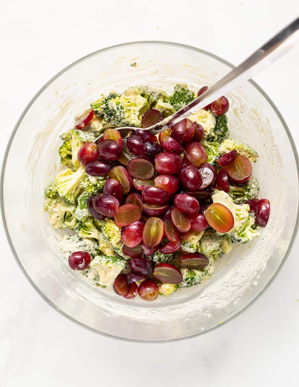 a bowl of broccoli tossed in creamy dressing with red grapes on top