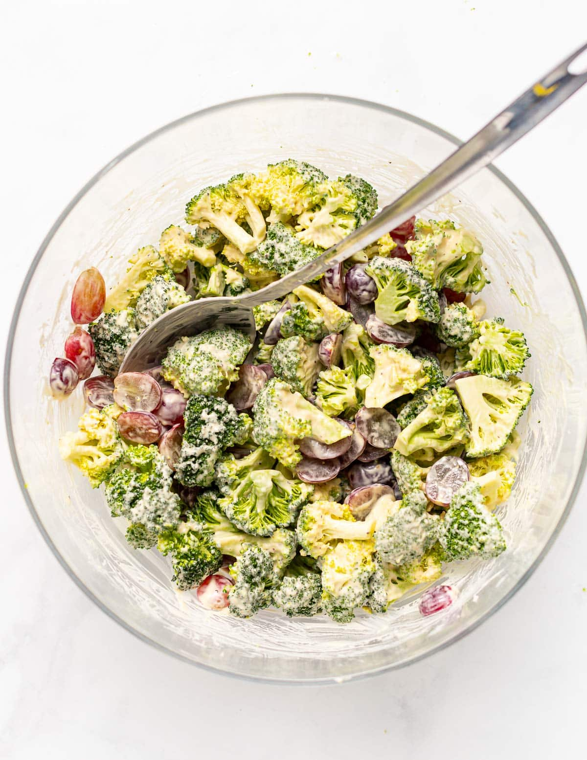 a bowl of vegan broccoli salad with a spoon in it