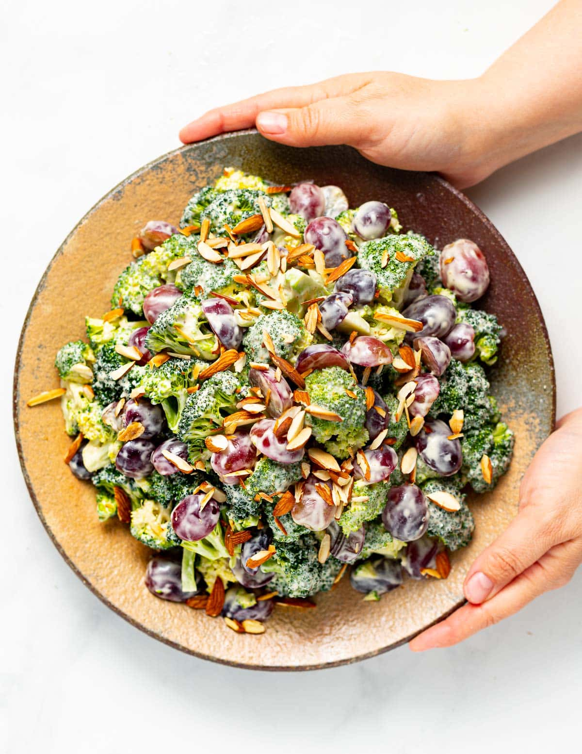 hands holding a rustic plate filled with vegan broccoli salad