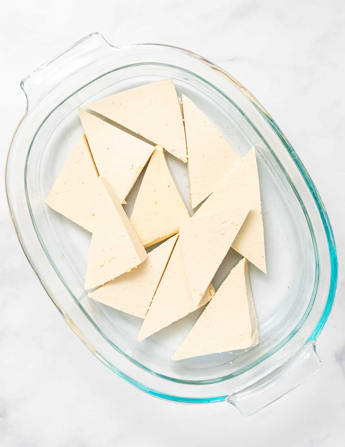triangles of tofu in a pyrex dish
