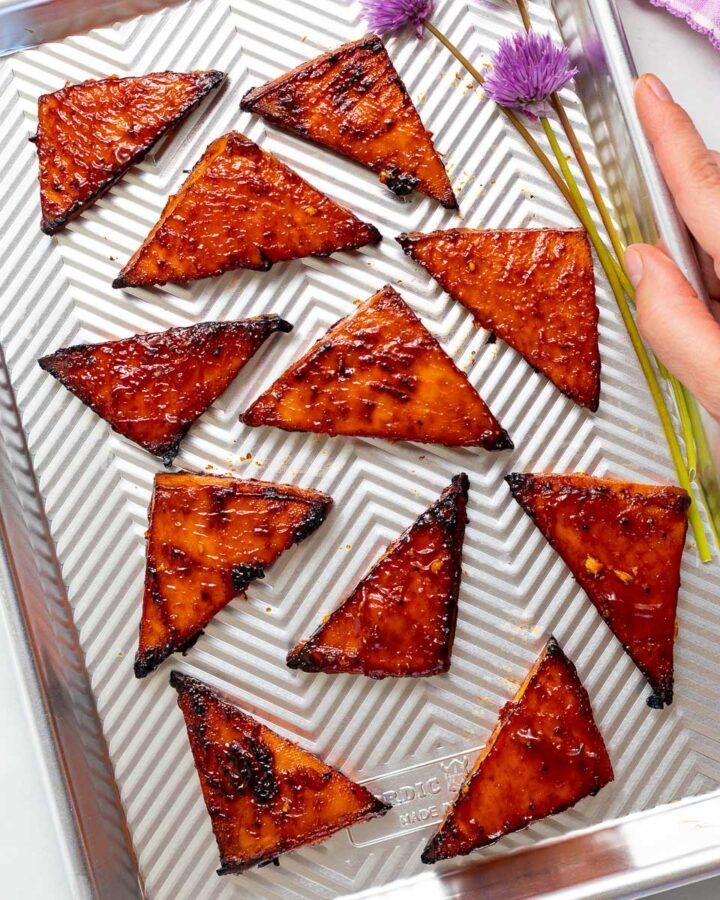 a baking tray with triangles of baked tofu and a couple of pretty chive flours