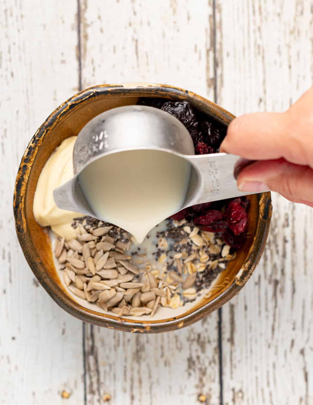 plant milk pouring into a bowl of oat, fruit and yogurt