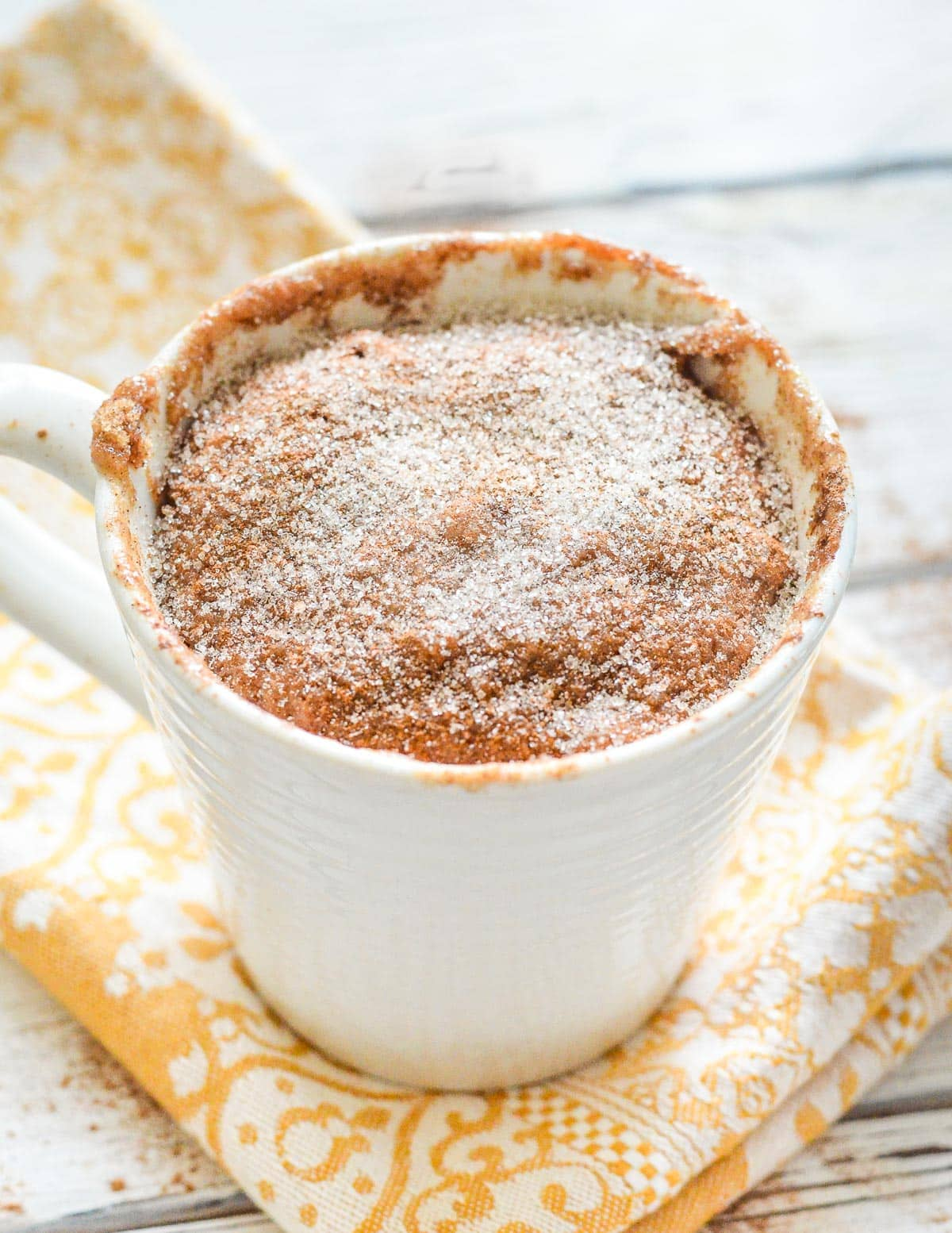 a snickerdoodle mug cake on a yellow napkin