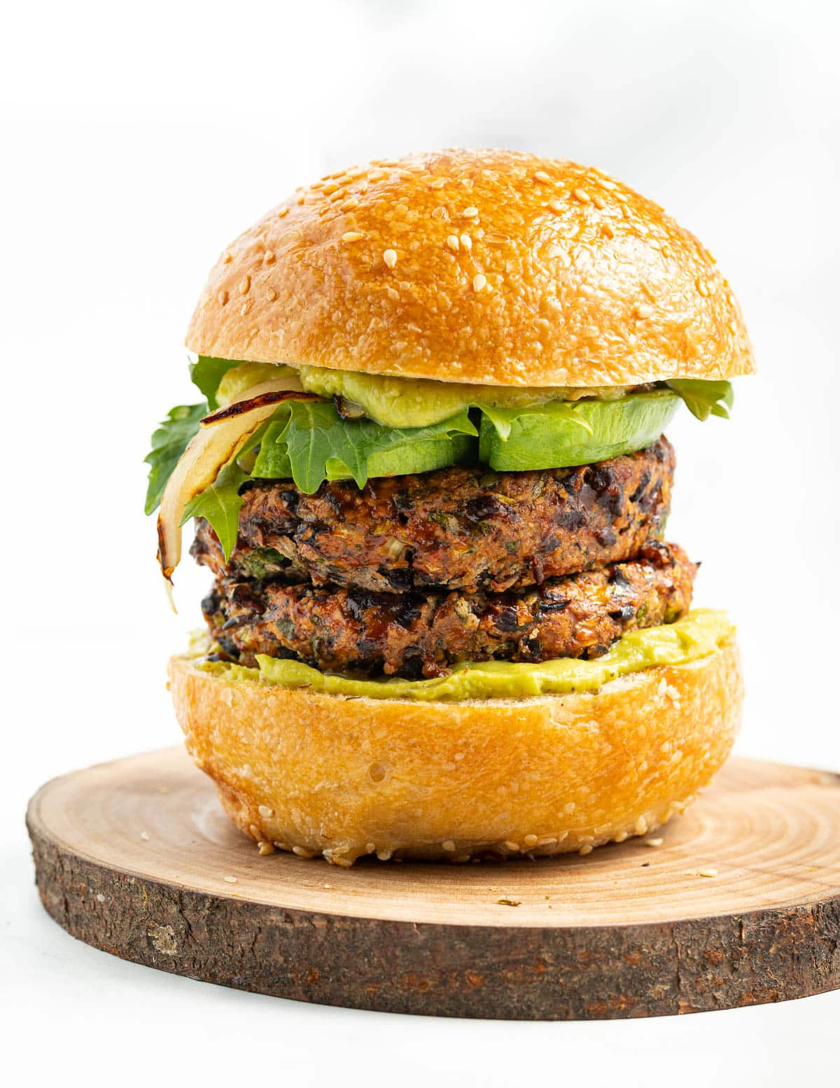 a double black bean burger stack in a bun with lettuce and avocado