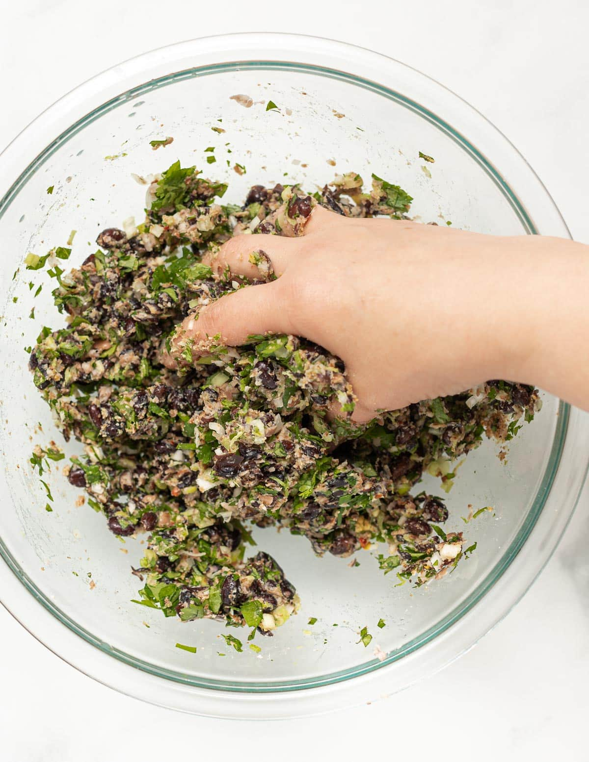 mixing bean burger ingredients with hands