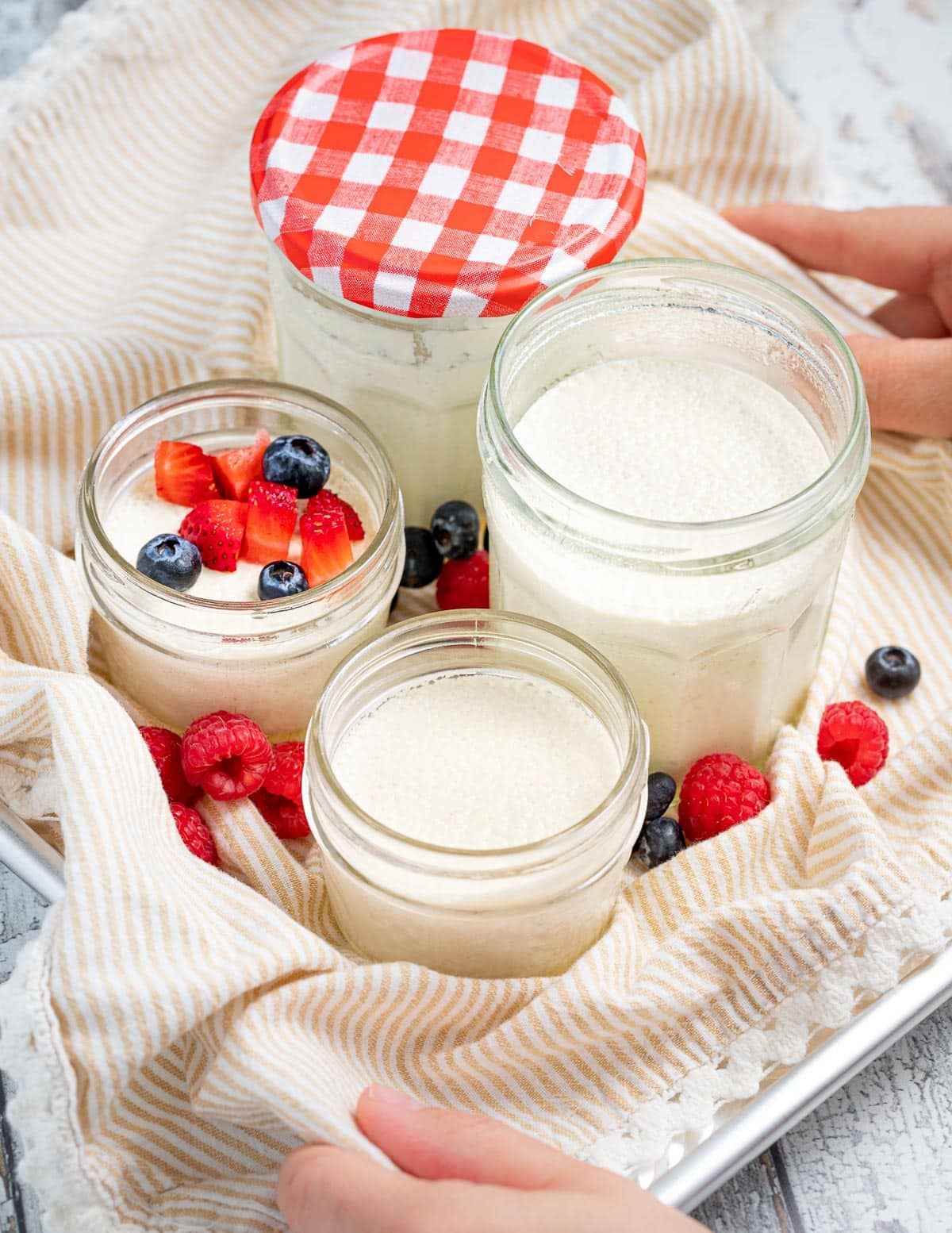 a tray with open jars of vegan yogurt on it