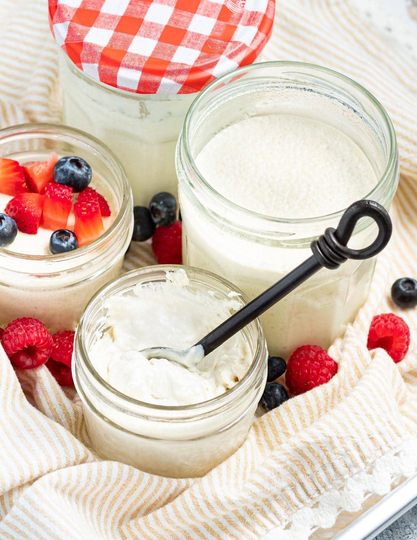 a jar of creamy vegan yogurt with a spoon in it
