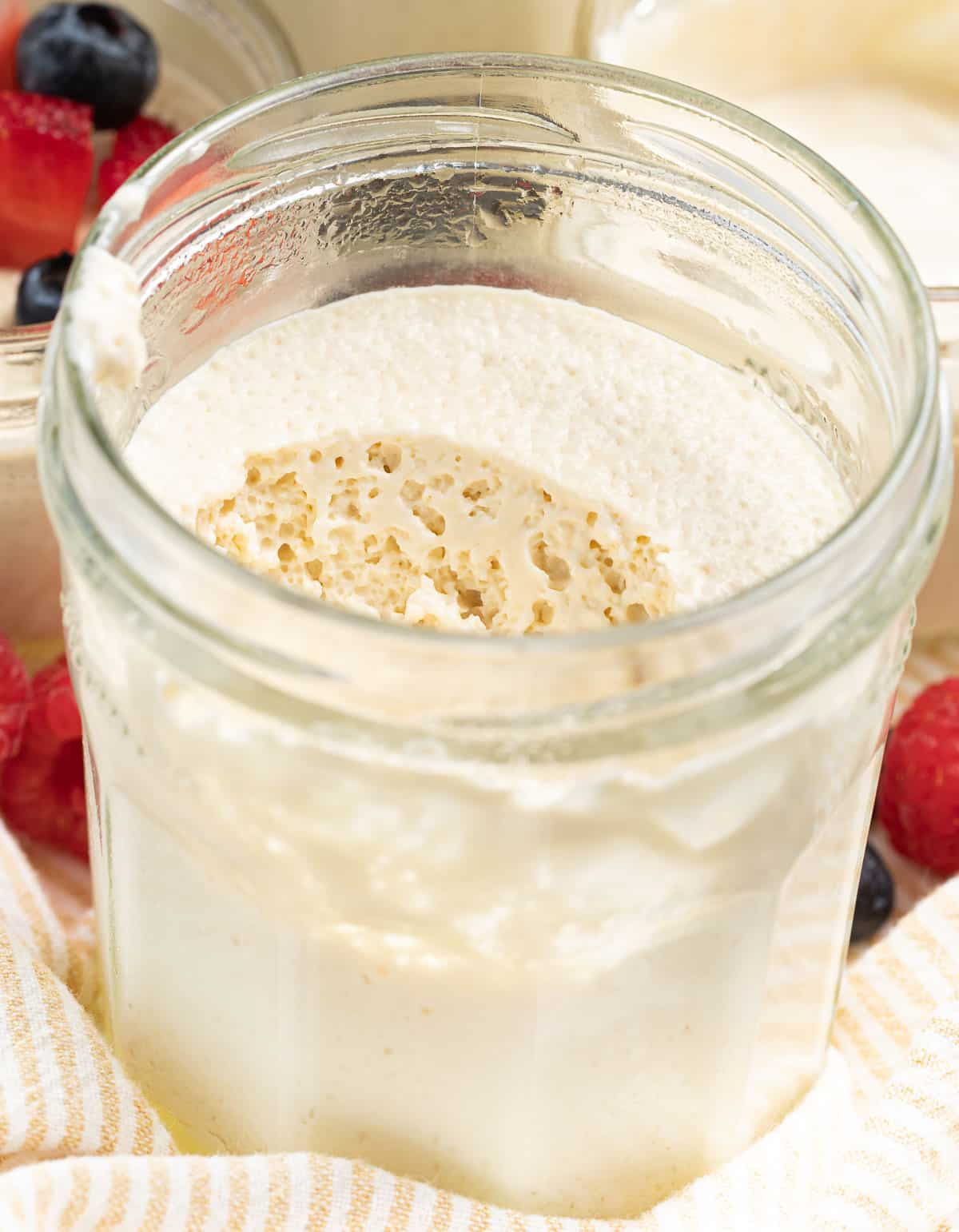 thick vegan yogurt in a jar with a spoon removed showing the bubbly fermented texture
