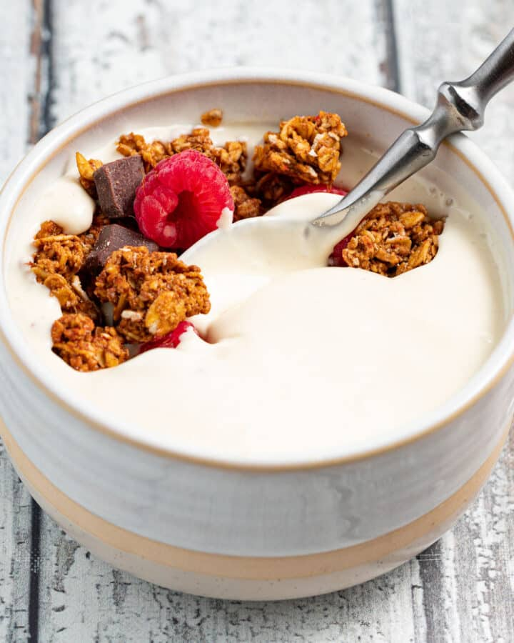 a bowl of vegan yogurt topped with granola and fresh raspberries
