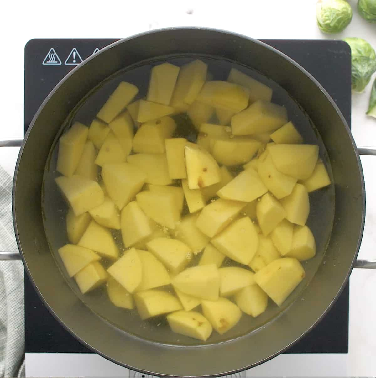 cubed potatoes in a pan of water