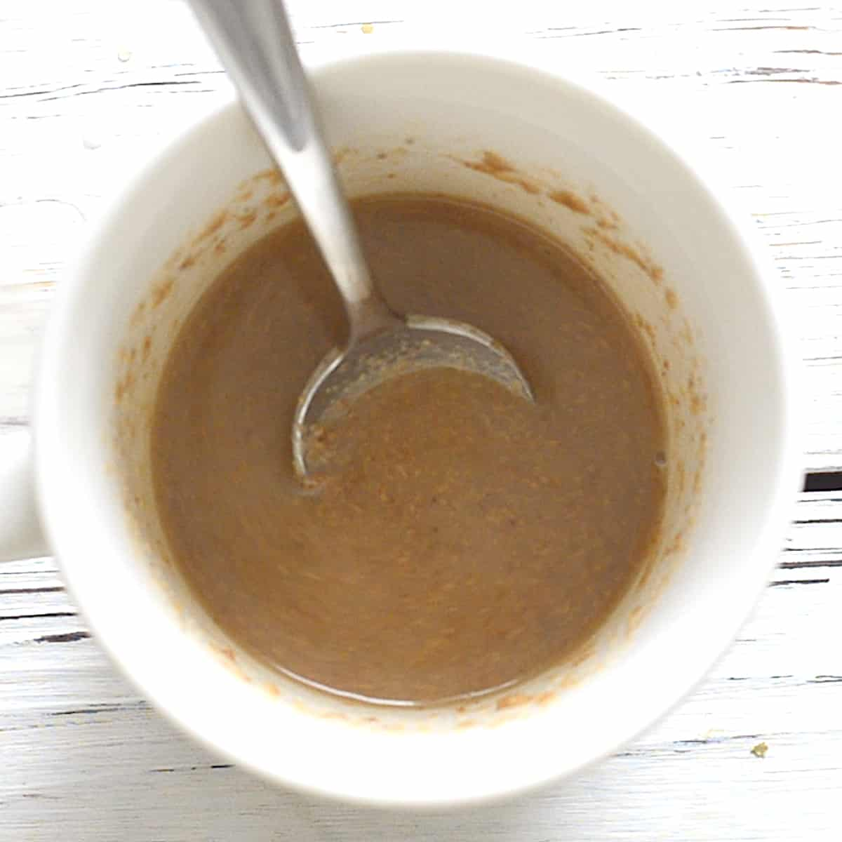 a mug with nut butter, plant milk and vanilla mixed up in it