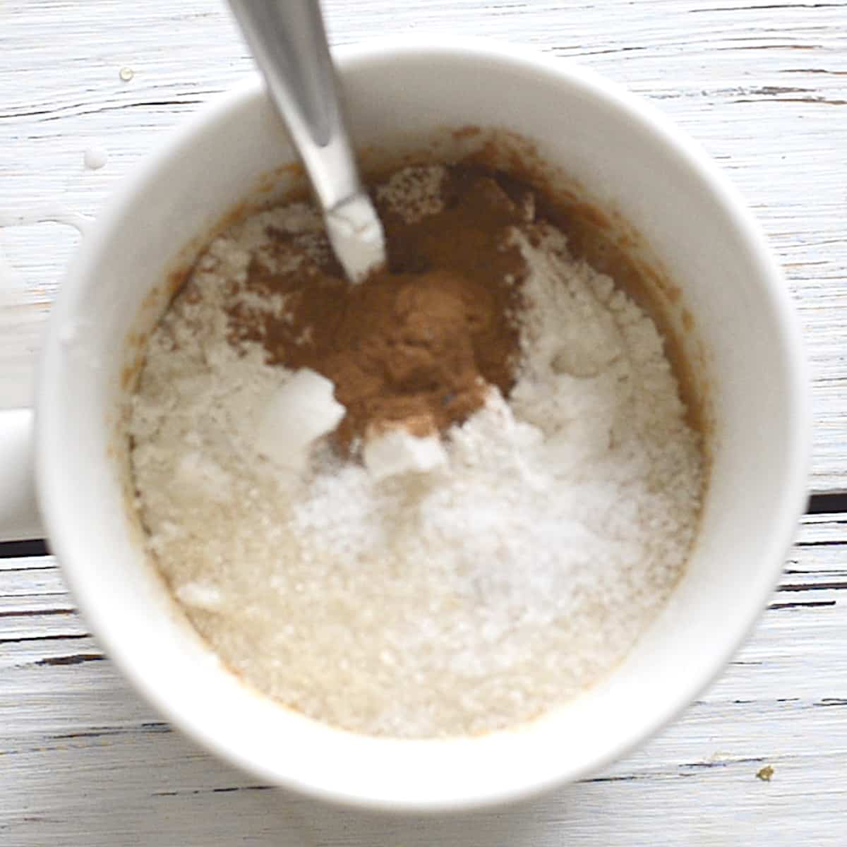 a mug with flour, cinnamon and sugar in it