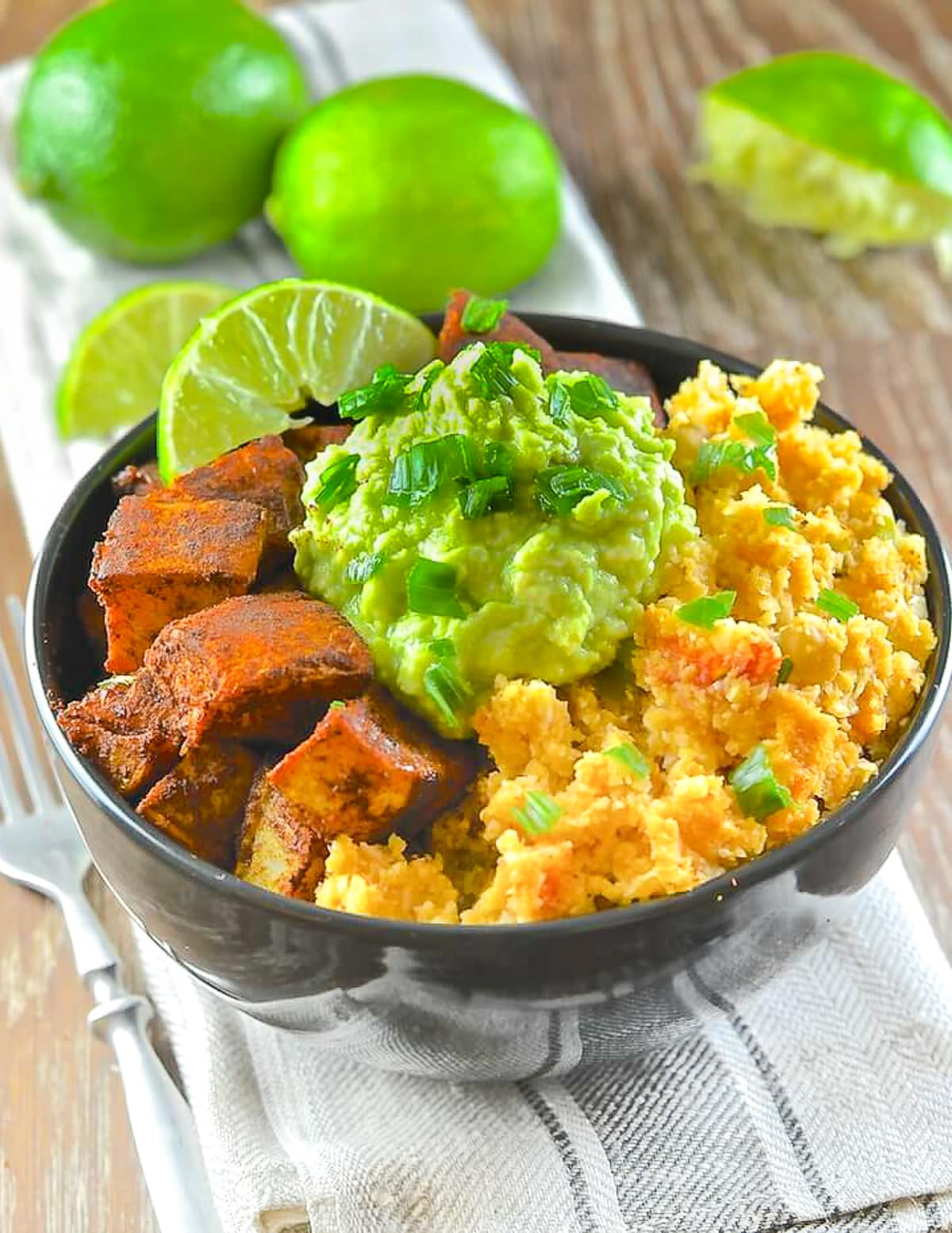 a bowl full of cauliflower rice, sweet potatoes, and avocado mash