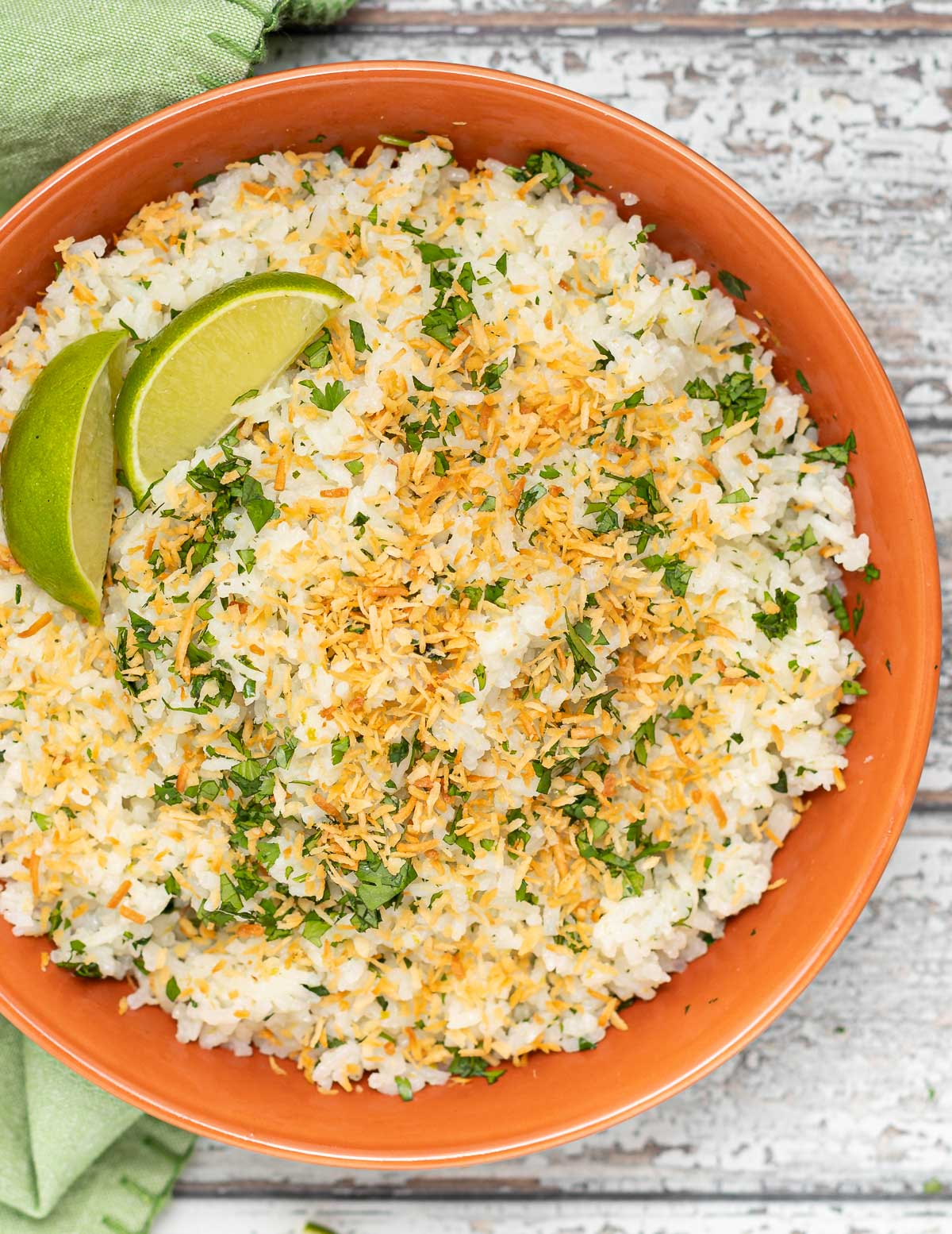 close up of coconut lime rice in a bowl with toasted coconut and cilantro