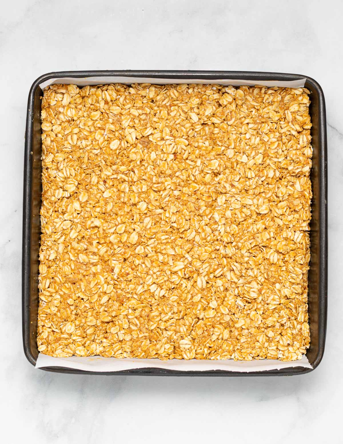 no bake oatmeal peanut butter bar mixture packed in a lined pan