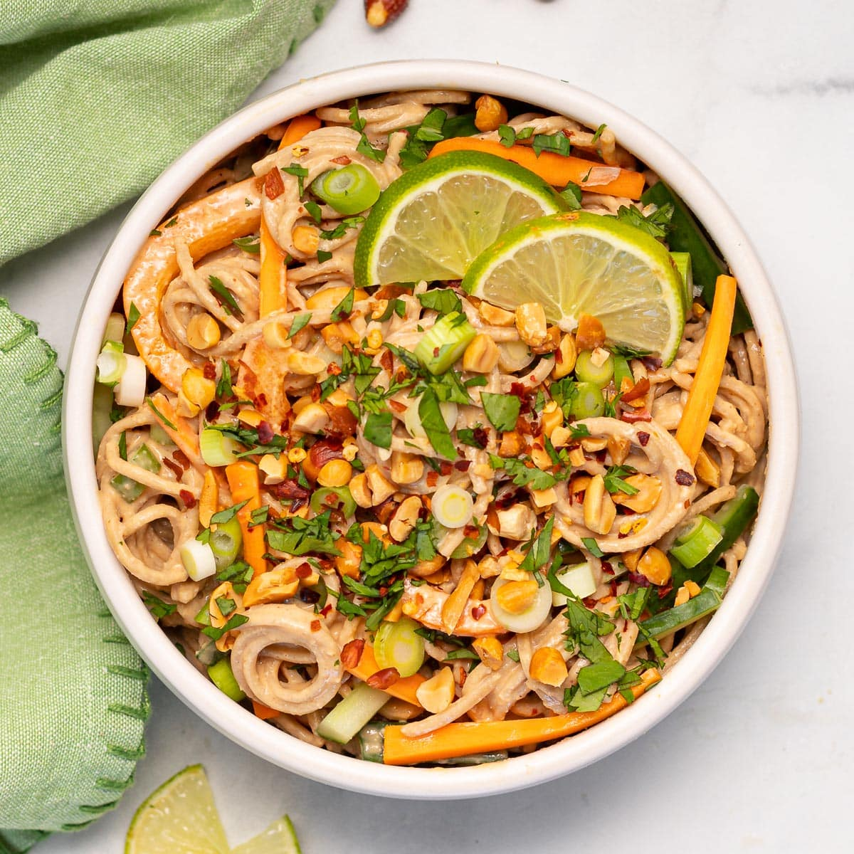 a bowl of peanut noodles with fresh vegetables and cilantro