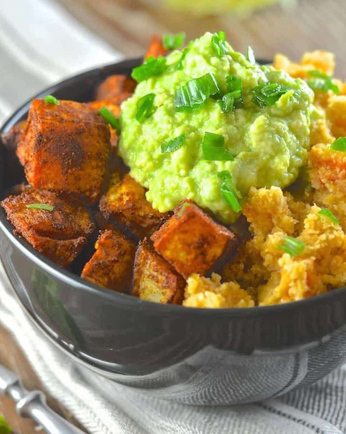 close up of roasted sweet potatoes on a cauliflower rice bowl