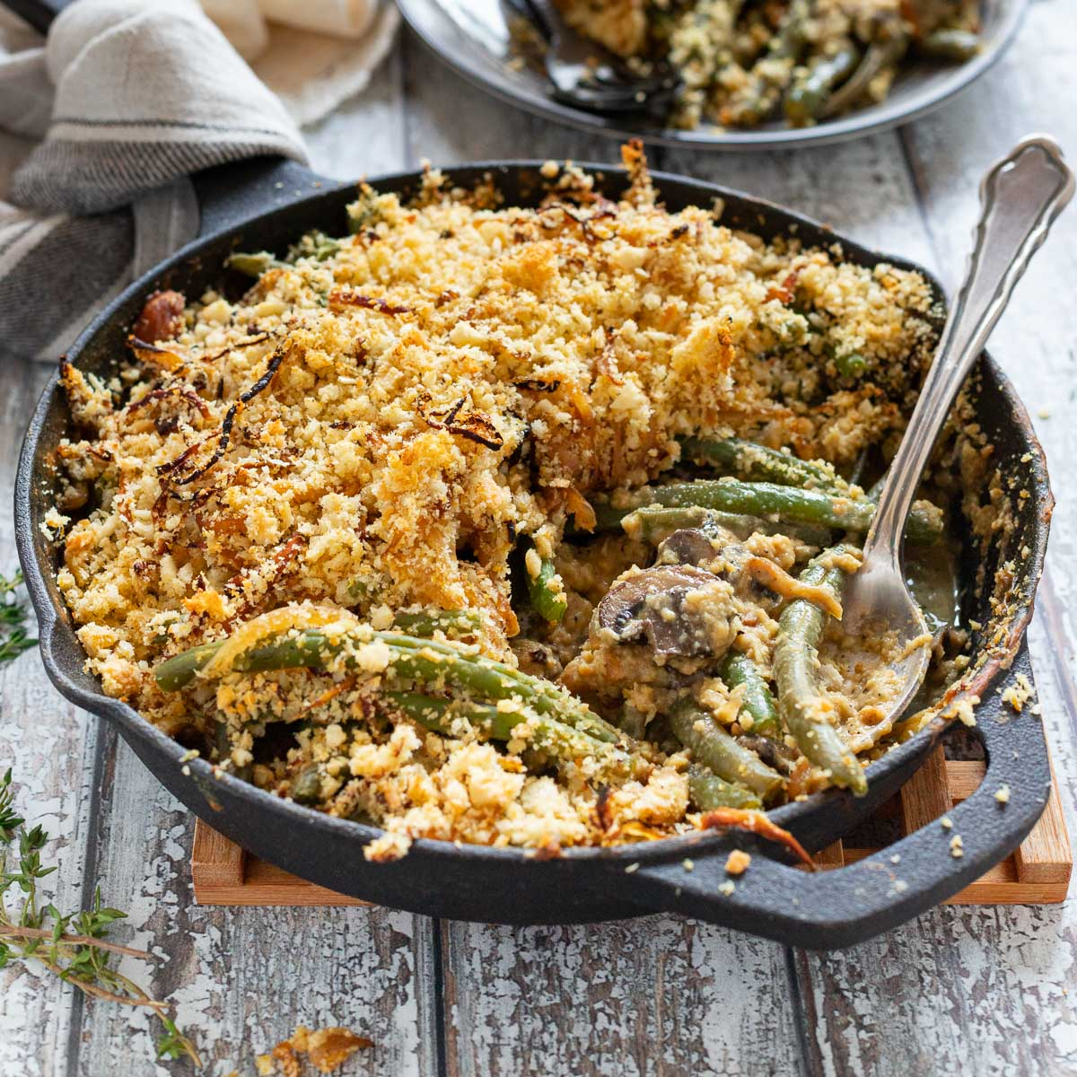 a skillet full of green bean casserole with a spoon in it