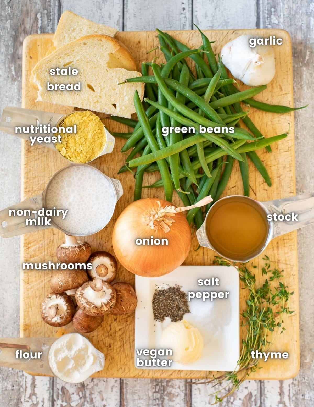 the ingredients for vegan green bean casserole on a wooden board