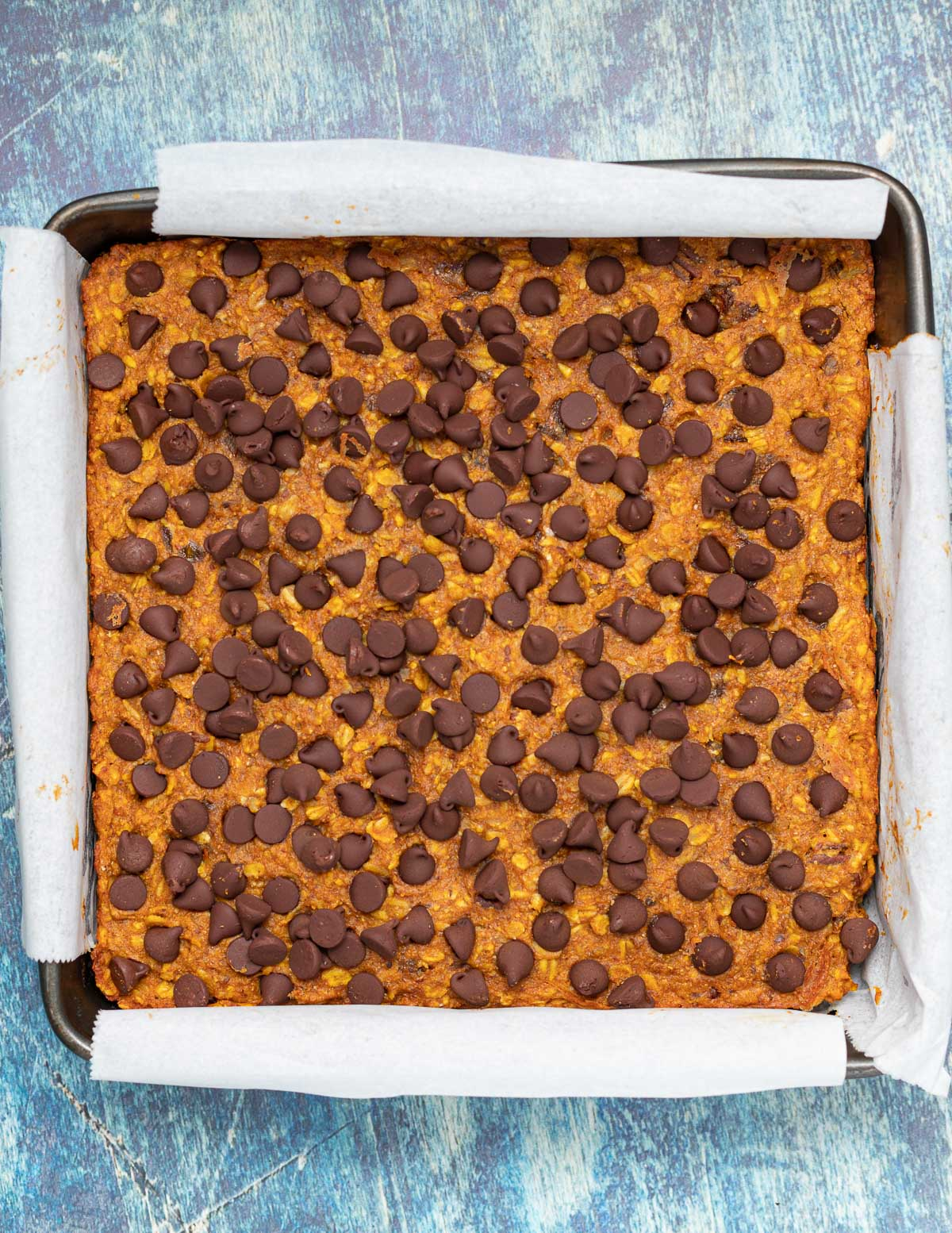 a pan of uncut oatmeal bars with chocolate chips on top