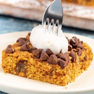 a fork being stuck into a pumpkin oatmeal bar with yogurt