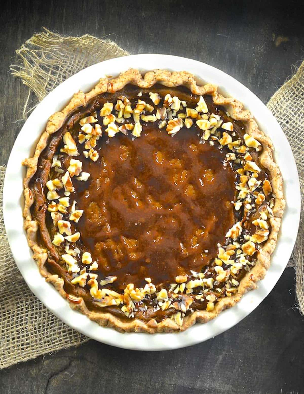 a vegan pumpkin pie topped with caramel and nuts