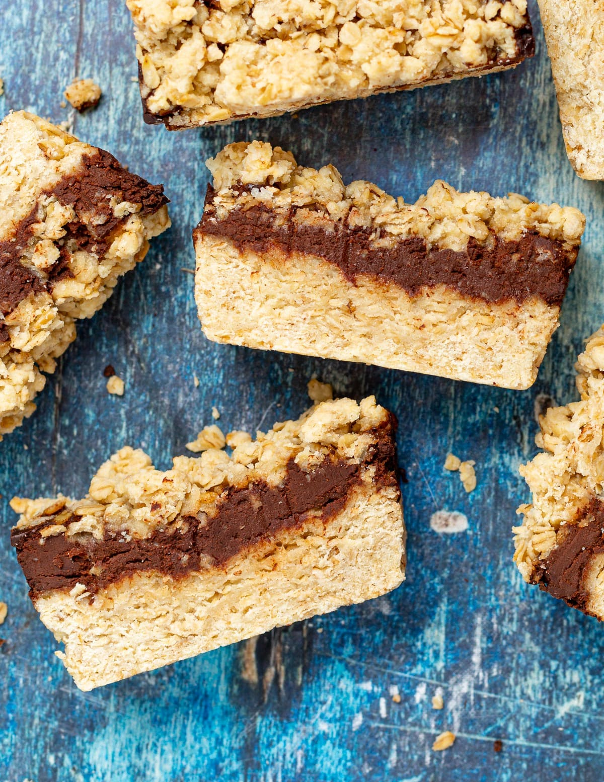 chocolate oat bars laid down on a blue background