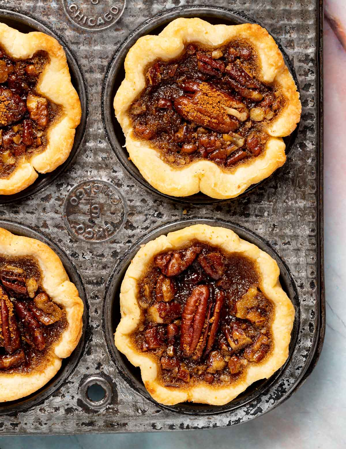 2 vegan butter tarts in a vintage muffin pan